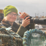 Jeni Reid in knitwear and action taking pictures on the Scottish coast.